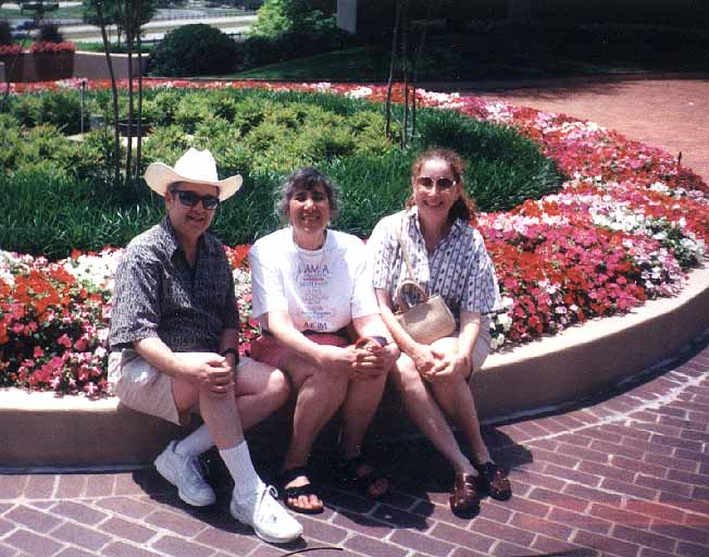 Bernie, Sue and Denise Mayoff in front of floral display