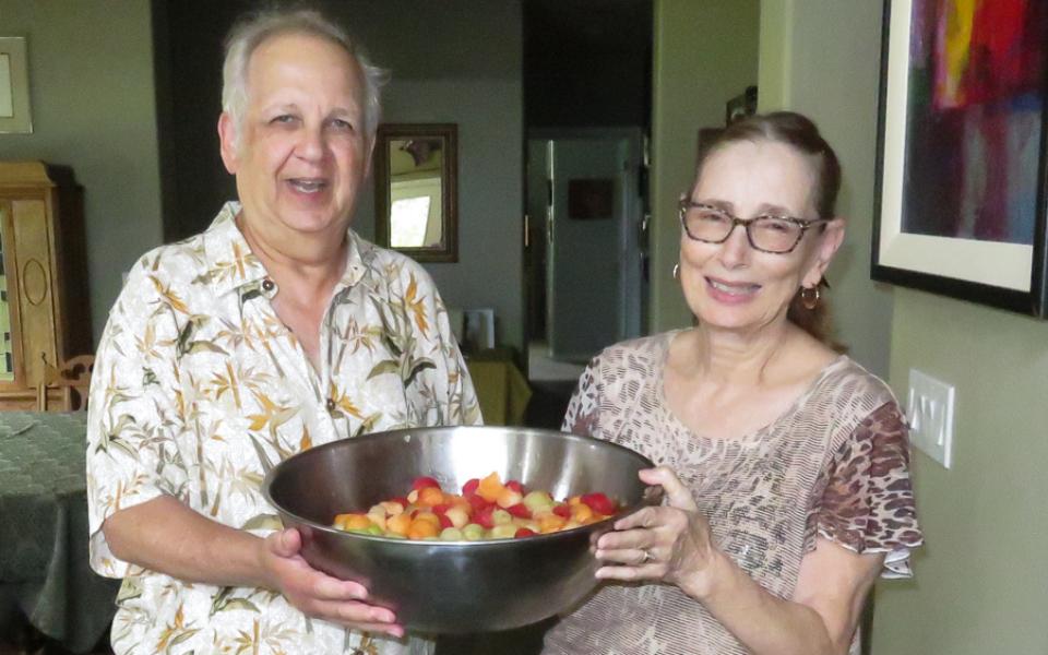 Bernie and Denise holding fruit salad bowl